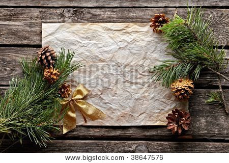Old crumpled paper with spruce twigs and golden bow. Sweet Xmas holiday background.