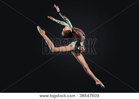 Young cute woman in gymnast suit show athletic skill on black background