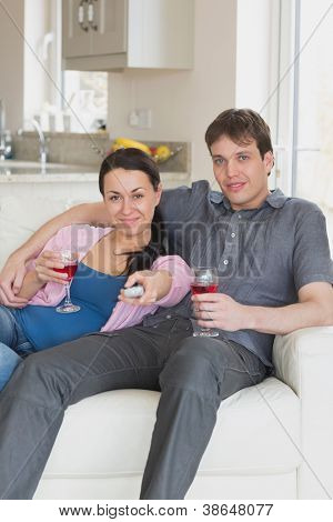 Young couple sitting on the couch while watching television and drinking wine