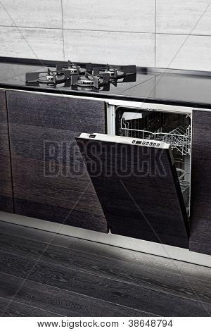 Offene Geschirrspüler Maschine und Gas-Herd auf schwarzem Hartholz Küche