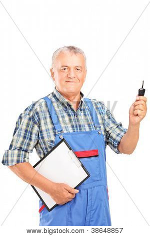 Mature mechanic in uniform holding a car key and clipboard isolated on white background