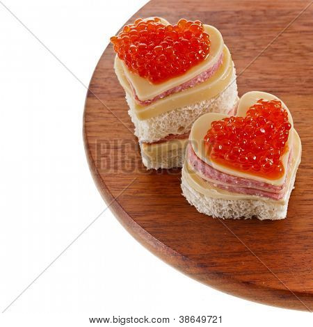two sandwich with red caviar in the form of a heart isolated on white