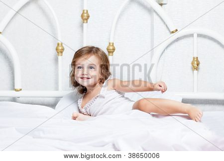 Cheerful sweet little girl lying in bed
