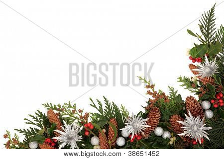 Christmas decorative border of holly, ivy, mistletoe, cedar leaf sprigs with pine cones, silver baubles and thistle sprays, emblem of scotland over white background.