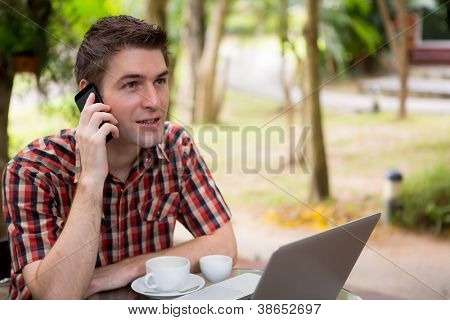 Business man sitting at table in cafe using mobile phone and laptop