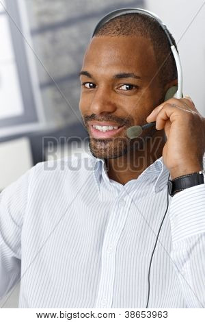 Closeup portrait of smiling handsome Afro-American customer service representative working with headset.