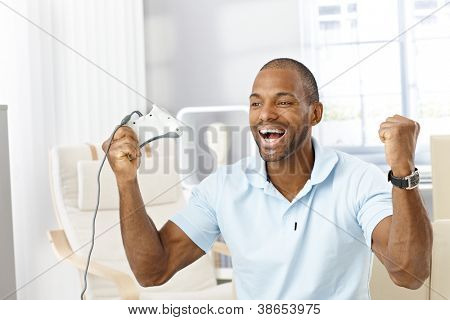 Portrait of laughing black guy happy winning computer game at home, holding joystick, raising arms.