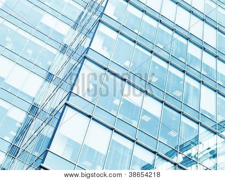 Perspective and underside angle view to textured background of modern glass building skyscrapers at night