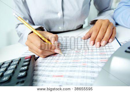 Foto de manos humanas sosteniendo el lápiz y marcar números en documentos
