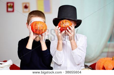 Photo of twin eerie boys holding Halloween pumpkins in front of their faces