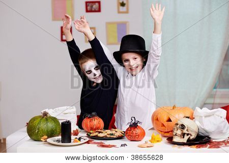 Photo of twin eerie boys raising arms in joy at Halloween table