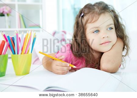 Portrait of lovely girl drawing with colorful pencils