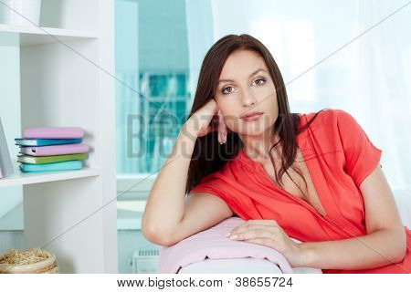 Portrait of calm woman looking at camera while resting at home