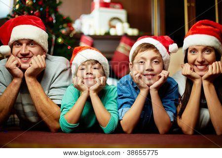 Retrato de familia en tapas de Santa mirando a cámara en noche de Navidad