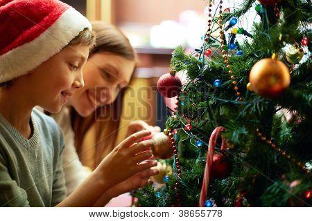 Retrato de niño feliz en tapa de Santa, decorar el árbol de Navidad