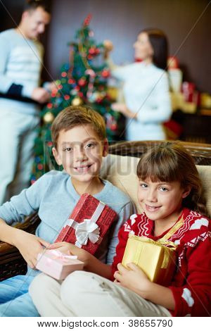 Portrait of happy siblings with giftboxes looking at camera with their parents on background
