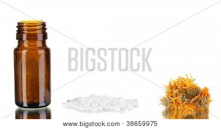 bottle with pills and herbs on white background. concept of homeopathy