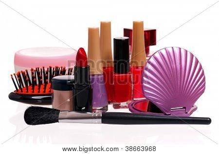 Set de cosmética - pequeño espejo, peine, esmalte de uñas y lápiz labial sobre fondo blanco