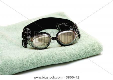 Gafas para nadar ponen en la toalla en blanco