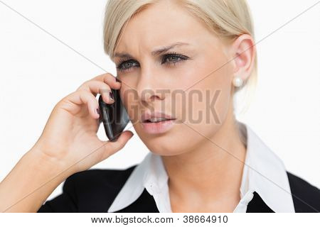 Serious blond businesswoman on the phone against white background