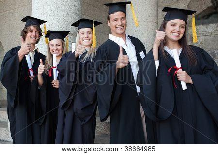 Graduados posando el pulgar arriba frente a la Universidad
