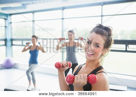 Smiling woman lifting weights while women doing aerobics in gym