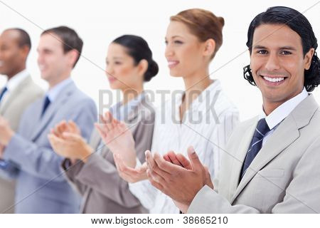 Close-up of a business team smiling and applauding while looking towards the left side except for one against white background