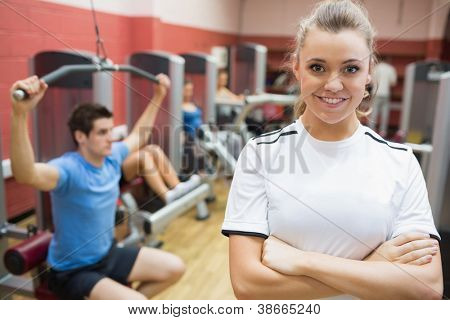 Female trainer smiling in front of class in weights room in gym