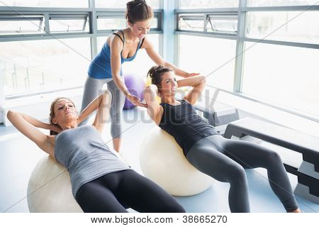 Two women doing sit-ups exercise balls in gym with trainer