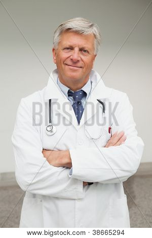 Smiling doctor with arms crossed outside hospital
