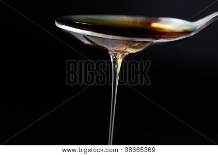 Honey trickle dropping of a spoon against a black background