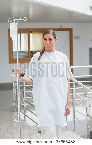 Female patient holding a drip stand in the corridor in hospital