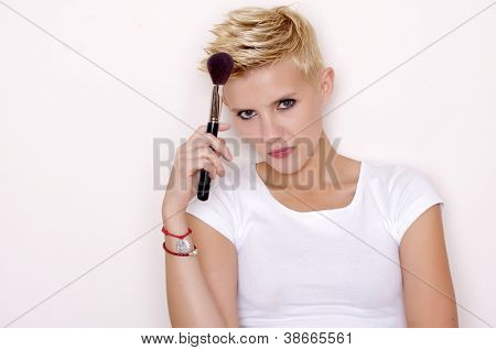 Atraente loira maquiador segurando escovas