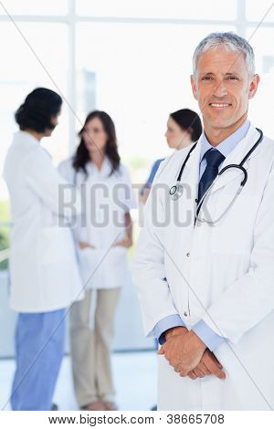 Mature and confident doctor crossing his hands in front of his medical interns