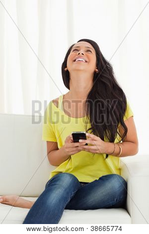 Happy Latino looking up while holding her cellphone being on a sofa