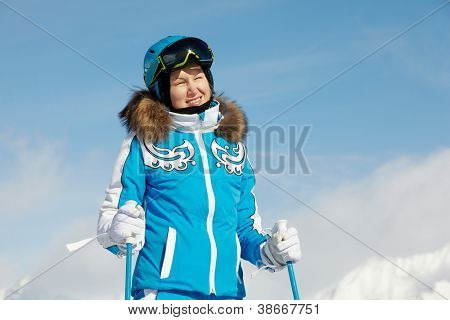 Young smiling woman in blue ski suit stands and looks, squinting in the sun