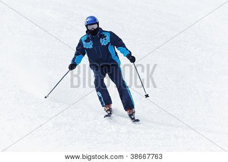 Man in darkblue ski suit glides downhill on skis