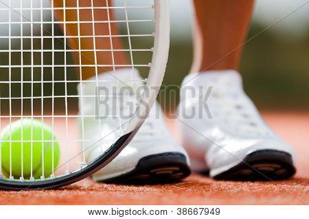 Piernas de niña deportiva cerca de la raqueta de tenis y pelotas