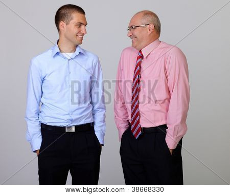 Happy smiling senior and junior businessman discuss something during their meeting with hands in pockets, isolated on grey