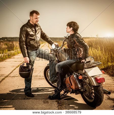 Biker man and girl sits on a bike