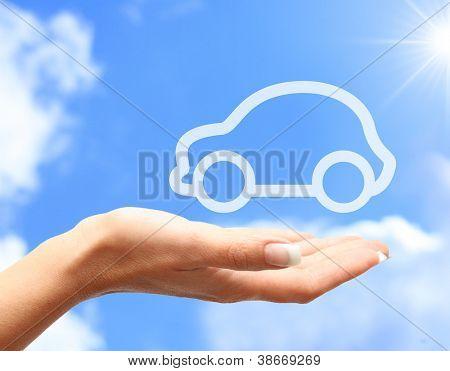Mano con el coche contra el fondo de cielo azul