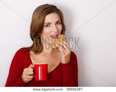 Beautiful woman drinking a hot coffee and eating a gingerbread cookie, against a gray wall