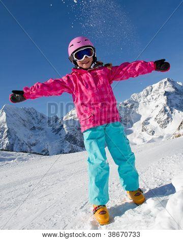 Winter fun, ski, snow and sun - lovely skier girl enjoying the snow