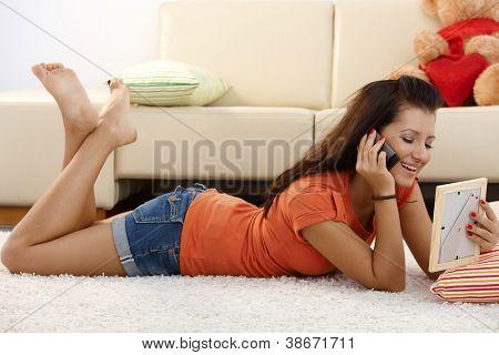 Hübsche junge Mädchen im Gespräch mit Freund auf Handy, Handauflegen Boden, sein Foto betrachten.