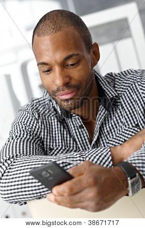 Retrato de homem de bem parecido preto sentado, mensagens de texto no telefone celular.