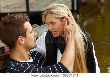 Young couple sitting on bench by lake, kissing.