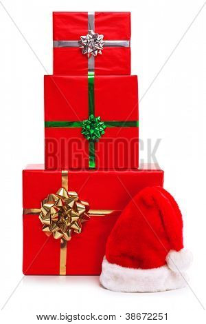 Santa Claus hat and three red gift wrapped Christmas presents with ribbons and bows, isolated on a white background.