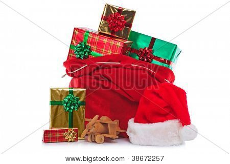 Photo of a red Santa Claus hat and sack full of gift wrapped presents and toys, isolated on a white background.