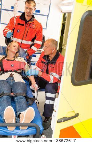 Paramedics help unconscious woman emergency ambulance measure blood pressure