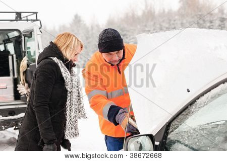 Woman mechanic looking under car hood snow assistance winter broken